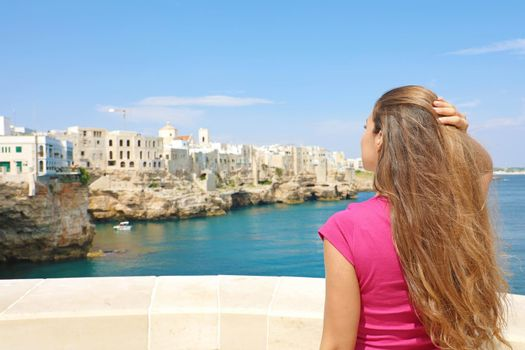 Portrait of beautiful young woman enjoying Polignano a mare view, Mediterranean Sea, Italy.