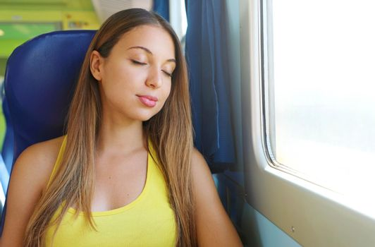 Traveler young woman sleeping in a train travels beside the window. Tired sexy lady take a nap. Girl sitting on seat on train or bus fell asleep in quiet place.