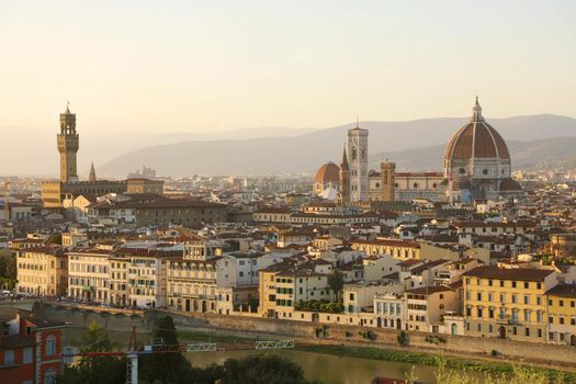 Florence city during golden sunset. Panoramic view of the river Arno with Palazzo Vecchio palace and Cathedral of Santa Maria del Fiore (Duomo), Florence, Italy.