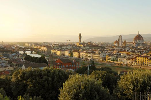 Florence city during golden sunset. Panoramic view of the river Arno with Ponte Vecchio bridge, Palazzo Vecchio palace and Cathedral of Santa Maria del Fiore (Duomo), Florence, Italy.