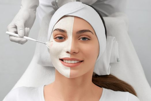 Beautician applying special white mask on face for woman.