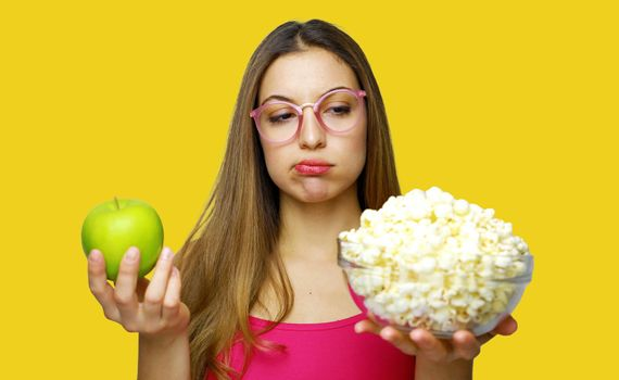 Woman choosing between unhealthy bowl of pop corn and an healthy green apple. Doubt about junk or healthy food.
