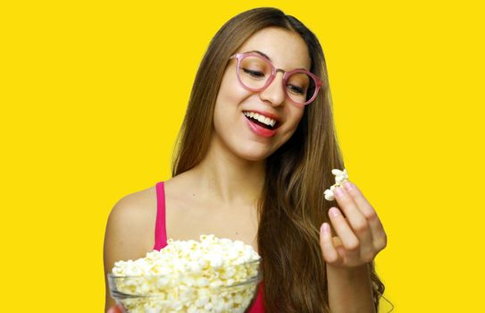 I love pop corn! Photo of young woman 20s holding bowl of pop corn while standing isolated over yellow background.