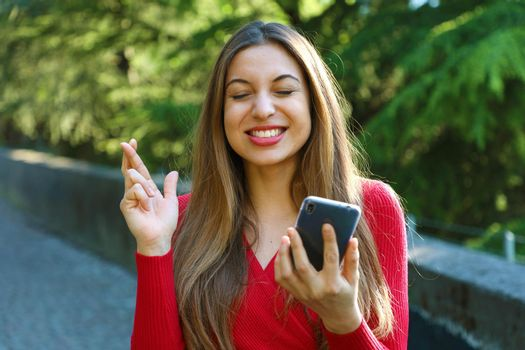 Hopeful girl crossing fingers holding a smartphone waiting for news outdoor. Young woman with crossing fingers and smart phone wishing the best outside.