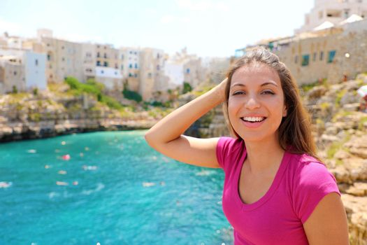 Summer holidays in Apulia. Portrait of beautiful girl in Polignano a mare town, Italy