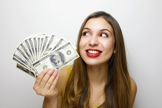 Image of delighted woman 20s holding fan of money in dollar cash and looking aside on copyspace with smile isolated over white background