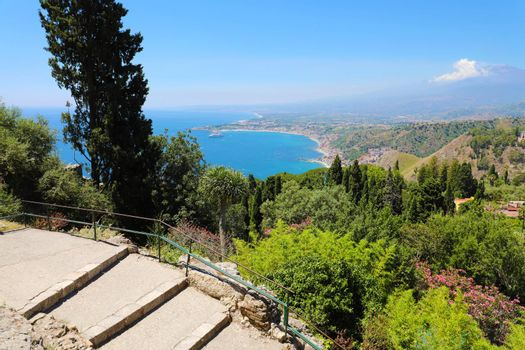 Beautiful aerial view of Sicily landscape with Etna volcano on the background. Blue Mediterranean sea and green mountians in Taormina, Sicily island, Italy.