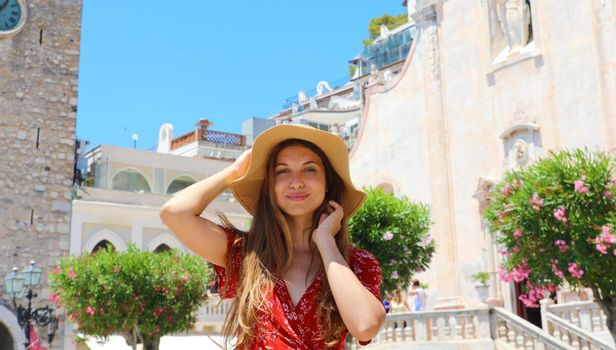 Beautiful smiling woman with hat in Taormina village on Sicily Island, Italy