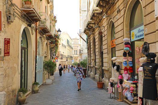 SYRACUSE, ITALY - JUNE 22, 2019: Narrow beautiful street in the island Ortigia, Syracuse, Sicily, Italy