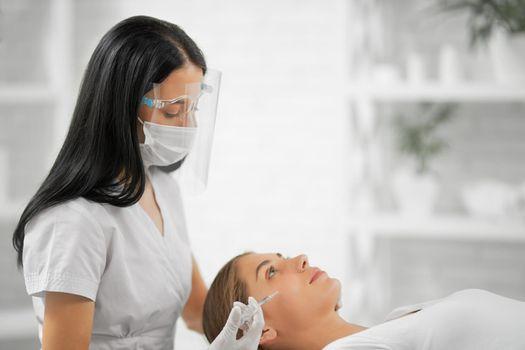 Woman lying on procedure injection anti-aging skin.