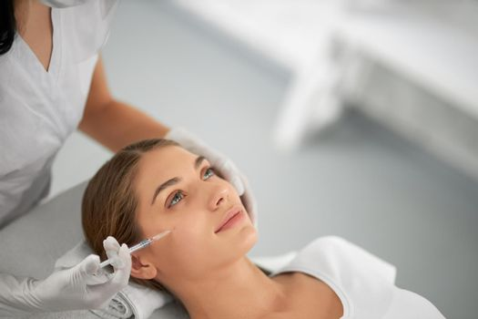 Young woman on procedure anti-aging in beauty salon.