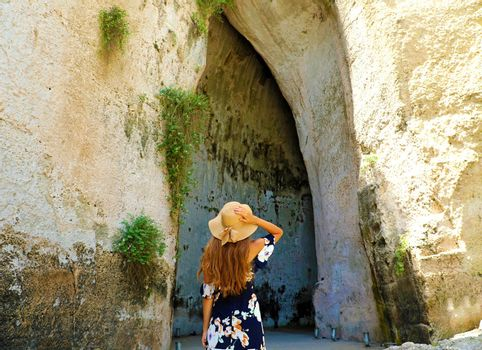Back view of beautiful woman comes into the Ear of Dionysius (Orecchio di Dionisio) in Syracuse, Sicily, Italy