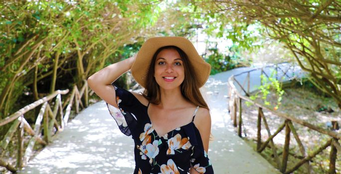Smiling happy woman with flowered dress and hat in park archway trees garden pathway banner panorama