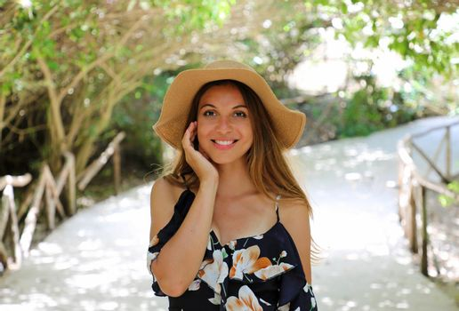 Beautiful cheerful woman with flowered dress and hat in park archway trees garden pathway