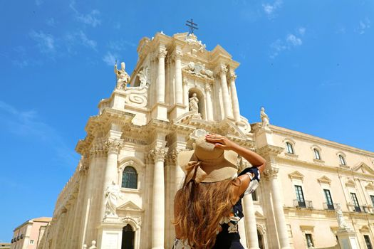 Beautiful young woman holding her hat and  looking to Syracuse Cathedral, Sicily, Italy