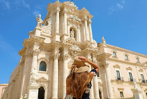 Travel in Sicily. Back view of beautiful girl visiting Syracuse Cathedral on sunny day. Summer holidays in Italy.