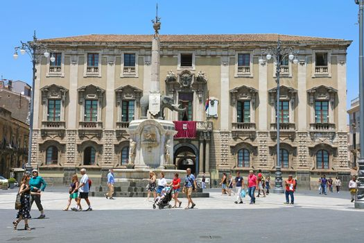 CATANIA, SICILY - JUNE 19, 2019: tourists in Piazza del Duomo square with the Elephant fountain obelisk and the city hall palace on the background, Catania, Sicily