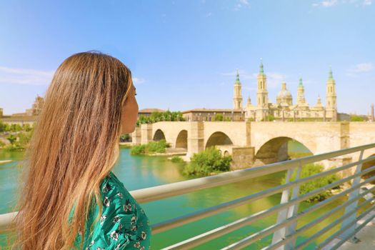 Beautiful young woman looking at Cathedral Basilica of Our Lady of the Pillar  in Zaragoza, Spain