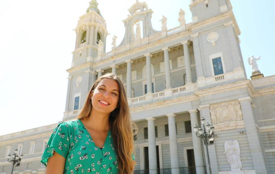 Portrait of smiling woman in Madrid with Almudena Cathedral on the background, Spain
