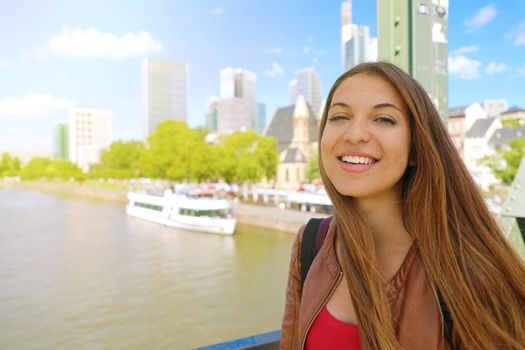 City tourism lifestyle in Germany. Smiling tourist woman on Frankfurt am main bridge with cityscape.