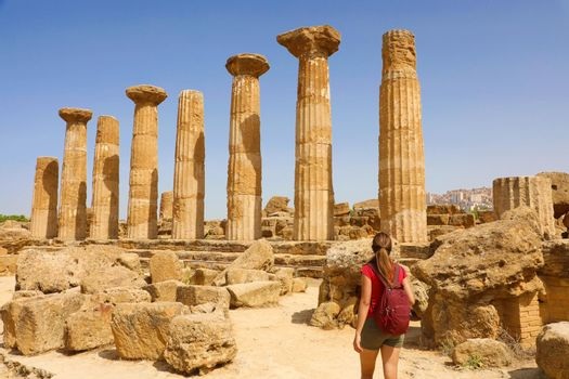Young woman walking in the Valley of the Temples of Agrigento, Sicily. Traveler girl visits Greek Temples in Southern Italy.