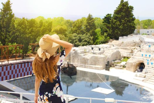 Beautiful elegant woman with hat and flowered dress in Syracuse Greek theater in Sicily, Italy, back view outdoors.