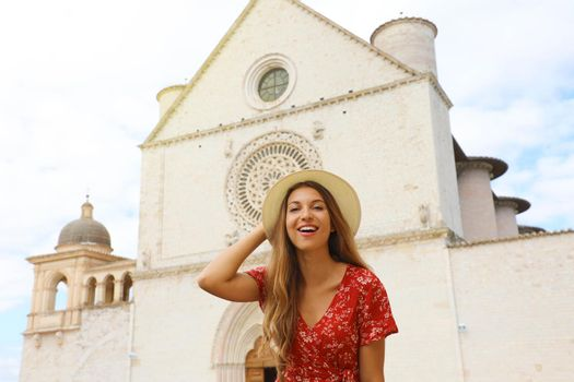 Portrait of beautiful girl in Umbria. Young fashion woman posing in front of Assisi Basilica of Saint Francis. Travels in Italy.