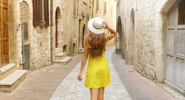 Back view of tourist woman holding hat and walking in typical medieval Tuscany street in Italy. Panoramic banner view.