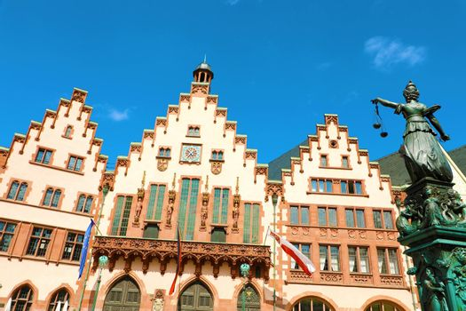 Romerberg square with the city hall and justice statue on blue sky, main landmark of Frankfurt, Germany
