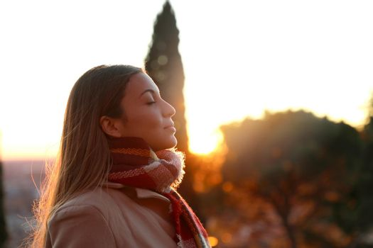 Portrait of a girl breathing fresh air wearing jacket at sunset
