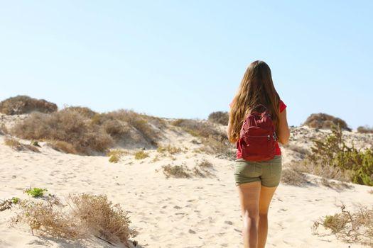 Female hiker backpacker walking in desert region of Fuerteventura, Canary Islands