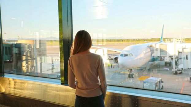 Passenger in an airport lounge waiting for flight aircraft