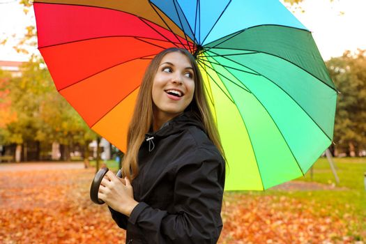 Cheerful young woman with colorful umbrella smiling back. Girl in park with raincoat and umbrella in the autumn.