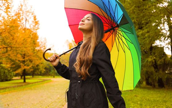 Portrait of a happy woman wearing raincoat under an umbrella breathing in city park on rainy day.