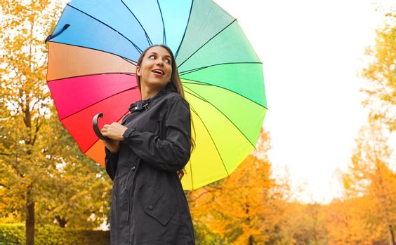 Pretty beautiful young woman under rainbow rain umbrella in the park looking to the side.