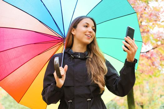 Beautiful young woman holding smart phone under rainbow umbrella in autumn outdoors.