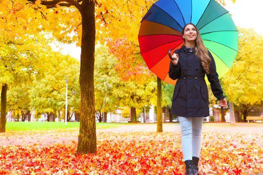 Autumn season. Young woman walking in city park under colorful rain umbrella.