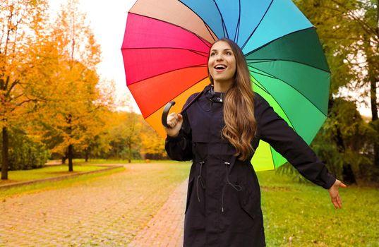 Pretty beautiful girl under rainbow rain umbrella in the park.