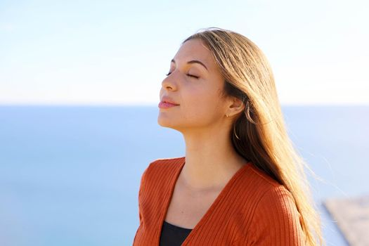 Close up of beautiful relaxed girl breathing fresh air with blue sea on the background.