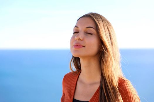 Close up of beautiful relaxed girl breathing and smiling with blue sea on the background.