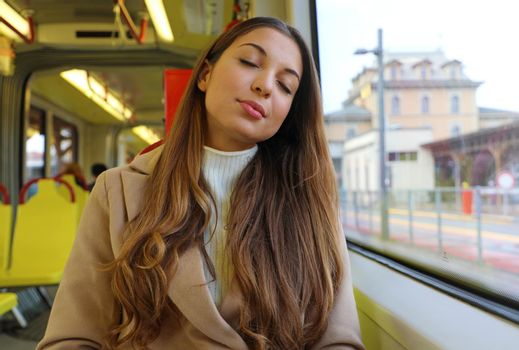 People on public transport. Tired young business woman take a nap on the tram.