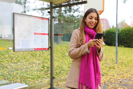 Young woman messaging with mobile phone waiting bus on bus stop.