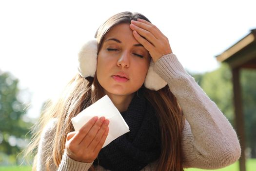 Young woman with earmuffs and scarf suffering migraine headache holding tissue outdoors.