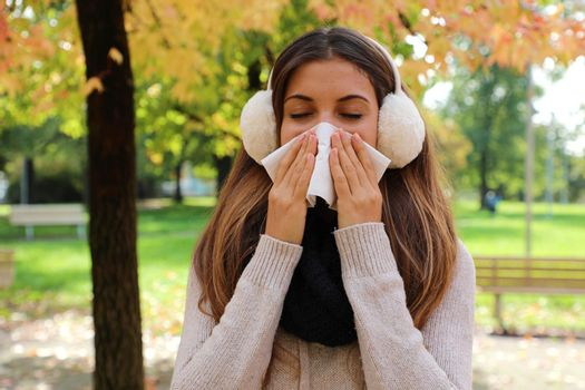 Young woman with earmuffs and scarf sneezing and blowing nose into tissue in city park.