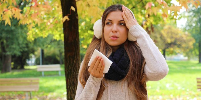 Winter flu banner view. Young woman suffering flu headache cold fever migraine holding tissue outdoors.