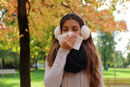 Student girl with earmuffs and scarf sneezing and blowing nose into tissue in city park.