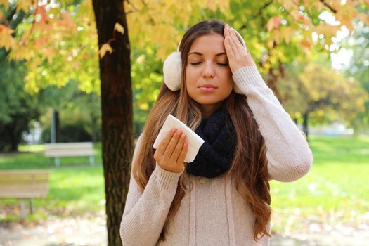 Young woman suffering headache cold fever holding paper tissue outdoors.