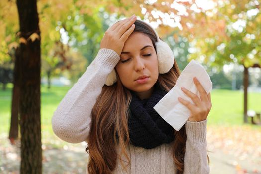 Woman suffering headache migraine holding tissue outdoors.