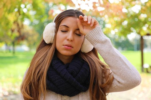 Girl with earmuffs suffering migraine headache fever outdoors.