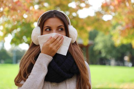 Young womanl with earmuffs and scarf sneezing and blowing nose into tissue looking to the side outdoors. Copy space.